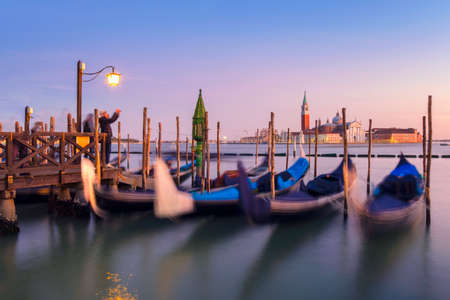 Venice with famous gondolas  in lagoon at sunrise as a background  can see the chucrh of San Giorgio Maggiore Banque d'images