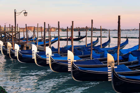 Row of gondolas parked on city pier on Grand Canal in Venice, Italy-Europe Archivio Fotografico