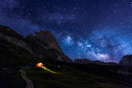 The night sky peppered with thousands of stars over Seceda Dolomites, Italy