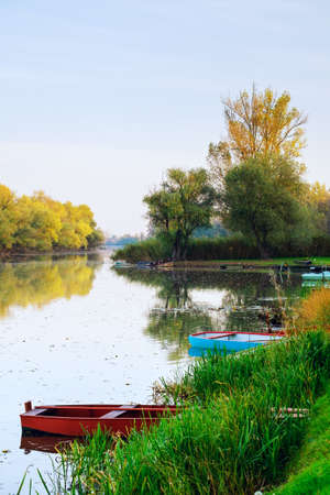 Old boat on the autumn pond in Tisza, Hungary Standard-Bild