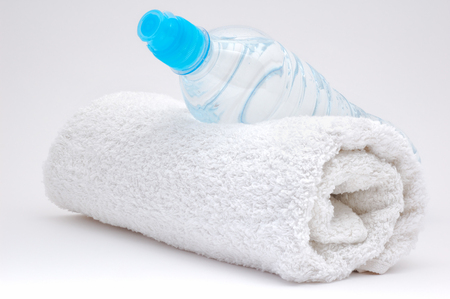 white towel: Bottle of water and  towel. Grey background