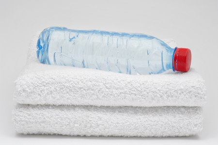 grey water: Bottle of water and towels. On grey  background