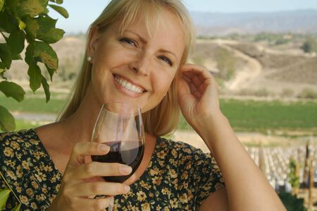 sipping: Beautiful smiling woman at a country winery tasting wine on a summer day. Stock Photo