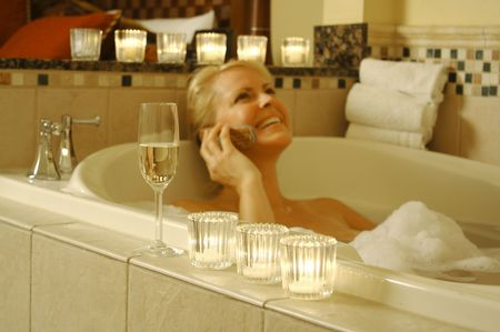Woman relaxing in a tiled tub. Sparkling wine, candles and towels adorn the scene. Stock Photo - 1311500
