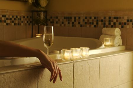 adorn: Woman relaxing in a tiled tub. Sparkling wine, candles and towels adorn the scene.