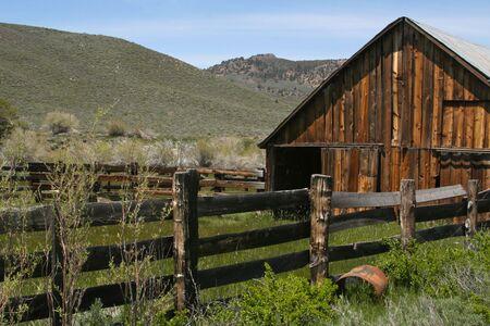 Genomen in de Sierras - rustiek, oude, verlaten boerderij en gras land. Rijk met oude houten hek, voederen troth en overwoekerd gras.  Stockfoto