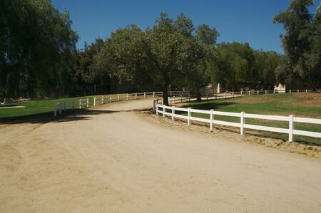 Country scene with white fence and dirt road.