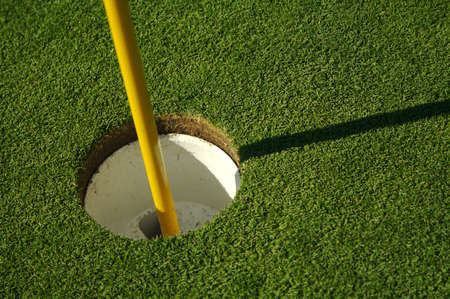 level playing field: Lush, freshly mowed golf green, flag and cup. Stock Photo