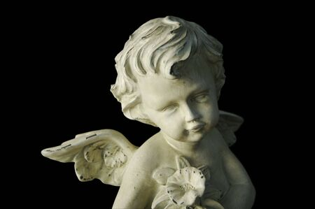 Cherub holding flowers with dramatic side lighting on a black background. Narrow focus on face of figure. Foto de archivo
