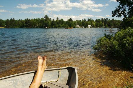 relaxes: Mujer se relaja en un bote de remos en un d�a de verano.