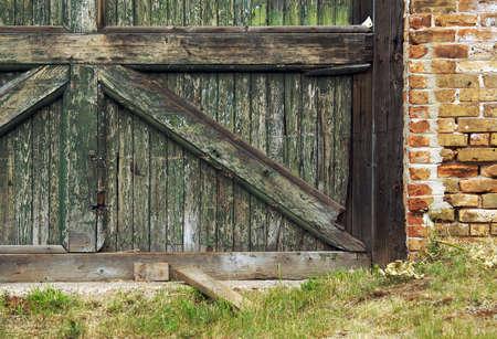 Abstract of abandoned barn door and brick wall. Stock Photo