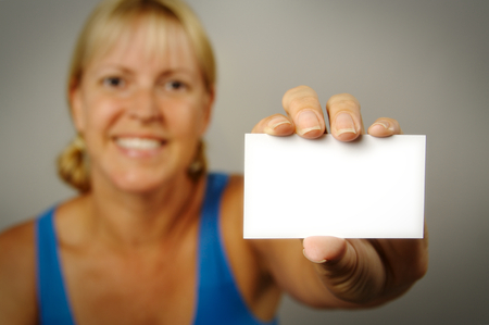 room for your text: Smiling Woman Holding Blank Business Card. Room for text, or your own message. Stock Photo