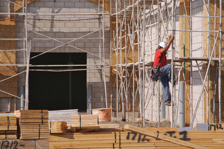 housing lot: Carpenter working diligently along scaffolding one summer morning. Stock Photo