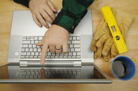 researches: Il handyman ricerca sul laptop con il pennello, rullo ed il legno mescola il bastone dal suo lato. Immagine grande per le informazioni in linea per quanto riguarda miglioramento, le aggiunte ed il ritocco domestici.