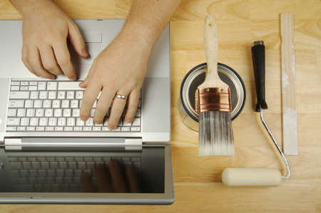 Handyman Researches on Laptop with paint brush, roller and wood stir stick by his side. Great image for online information regarding home improvement, additions and remodeling. Stock Photo - 1489342