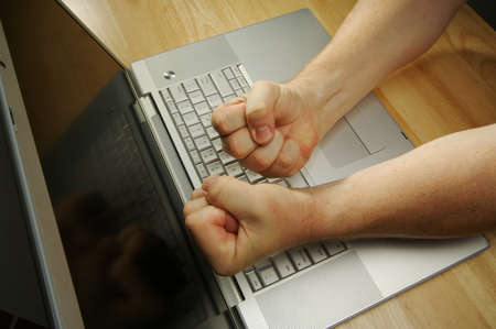 Frustrated businessman shows his frustration while working on his laptop. Stock Photo - 1489344