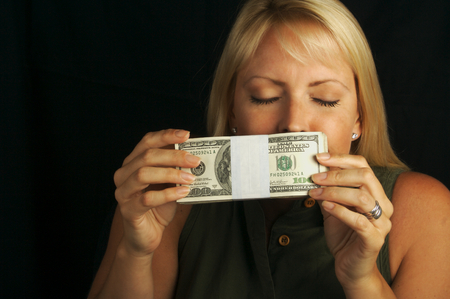 Attractive Woman Enjoys the Smell of Her Stack of Money on a Black Background Stock Photo - 1525789