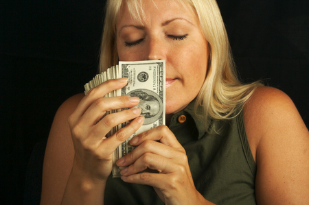 Attractive Woman Enjoys the Smell of Her Stack of Money on a Black Background Stock Photo - 1525794