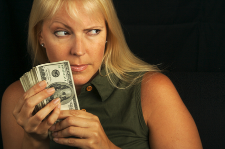Attractive Woman Getting Greedy About her Stack of Money on a Black Background Stock Photo - 1525795
