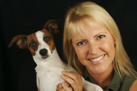 Attractive Woman Holds Her Jack Russell Terrier Dog on a Black Background photo