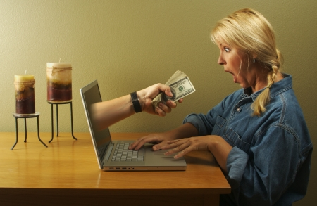 Working at home. Attractive businesswoman shocked to see a hand coming through her laptop screen handing her a stack of money. Can it be that simple? photo