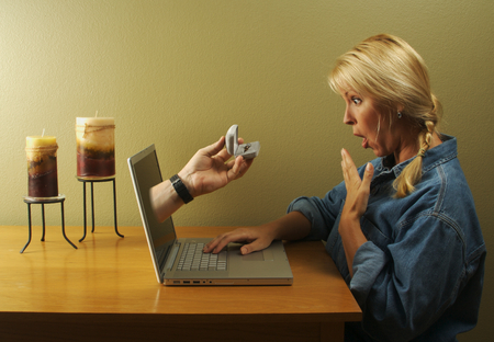 Online dating. Attractive woman surprised with her online proposal & ring coming through her laptop screen. Stock Photo - 1543844