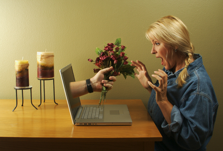Online dating. Attractive woman stunned from the flower handed to her coming through her laptop screen. Фото со стока
