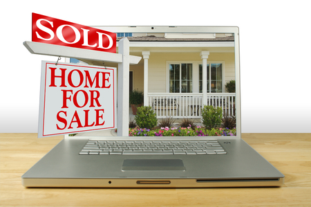 Verkocht Home for Sale Sign & New Home op Laptop Stockfoto