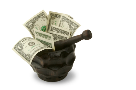 Grinding for Dollars - Wood mortar and pestle containing dollar bills on a white background. 版權商用圖片