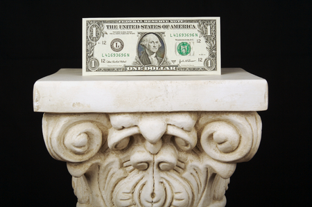 almighty: The Almighty Dollar - One dollar bill on a pillar with a black background. Stock Photo