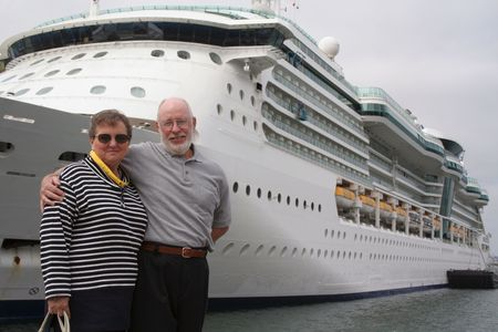 disembarking: Senior couple ready for another cruise in front of a cruise ship.