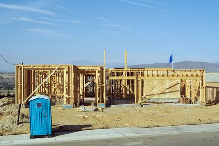 Construction site with new home framing and outhouse.