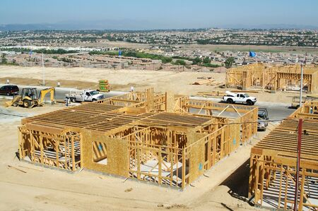 property development: New Home Construction Site with New Home Framing Stock Photo