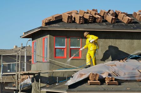 Construction worker pressure washes fresh applied surface of new home exterior. photo