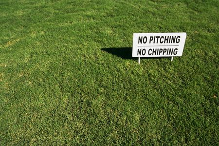 No Pitching, No Chipping sign in Lush Green Golf Course Grass. photo