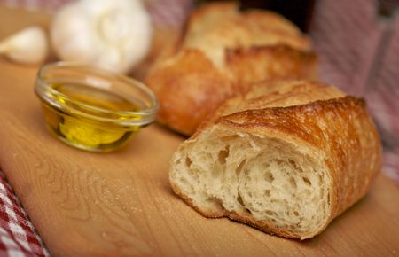 epicurean: Sourdough Bread on Cutting Board with Narrow Depth of Field Stock Photo