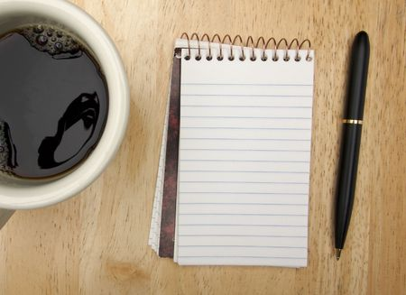 scribbling: Note Pad Coffee Cup and Pen on Wood Background