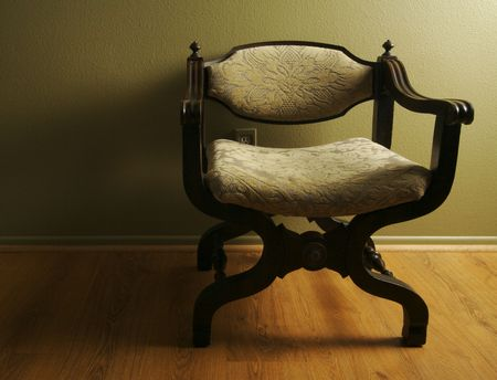 olive green: Roman Styled Chair Against an Olive Green Wall Stock Photo