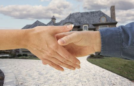 negotiation business: Man and woman shaking hands in front of a new house. Clipping path is included.