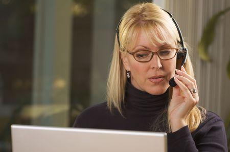 Attractive businesswoman talks on her phone headset. photo
