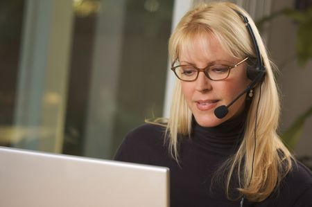 Attractive businesswoman talks on her phone headset. Stock Photo - 2562501