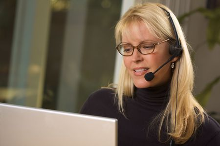 customer service representative: Attractive businesswoman talks on her phone headset.
