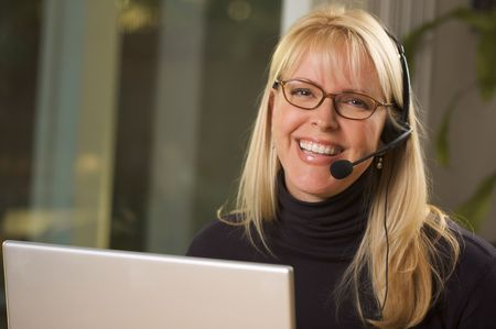 customer service representative: Attractive businesswoman smiles as she talks on her phone headset.