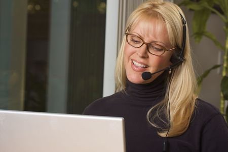 Attractive businesswoman smiles as she talks on her phone headset. photo
