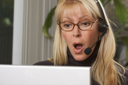 Attractive businesswoman galks in surprise while on her phone headset. photo