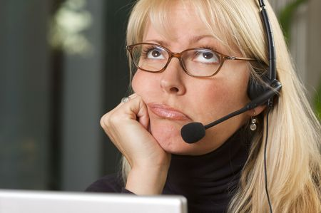 dullness: Attractive businesswoman talks on her phone headset.