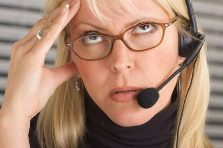 dullness: Businesswoman with phone headset show signs of having a headache. Stock Photo