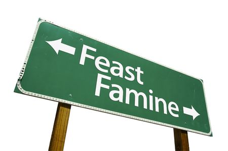 famine: Feast or Famine road sign isolated on a white background.  Stock Photo