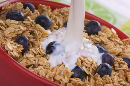 Milk being Poured into Bowl of Granola and Blueberries Stock Photo