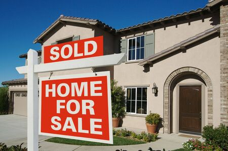 real estate sold: Sold Home For Sale Sign in Front of New House on Deep Blue Sky Stock Photo